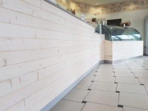 Progetto di ristrutturazione di una gelateria in stile scandinavo con bancone rivestito in legno sbiancato